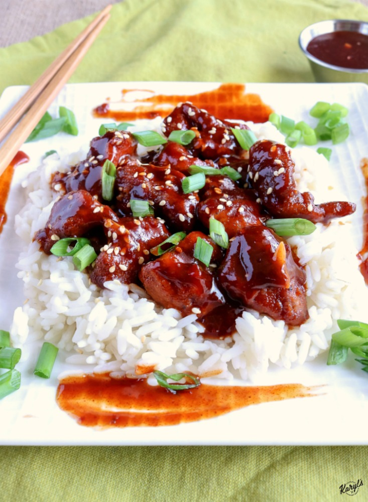 close up shot of finished Baked General Tso's Chicken over rice on a white plate with chopsticks on the side