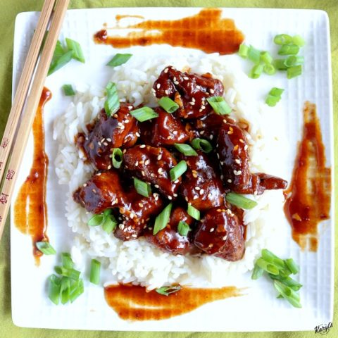 overhead shot of finished Baked General Tso's Chicken over rice on a white plate with chopsticks on the side