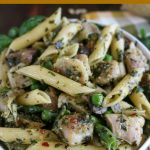 overhead close up shot of pesto chicken penne pasta in a white bowl