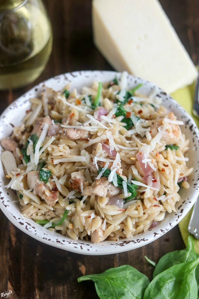 Peppery Parmesan Grilled Chicken Orzo is a bold and flavorful dish. Cooked with homemade broth and a dash of wine all in one skillet except the chicken, this dish is on the table in 30 minutes #pasta #orzo #grilledchicken #chicken #parmesan #babyspinach #redpepperflakes #cookingwithwine #karylskulinarykrusade