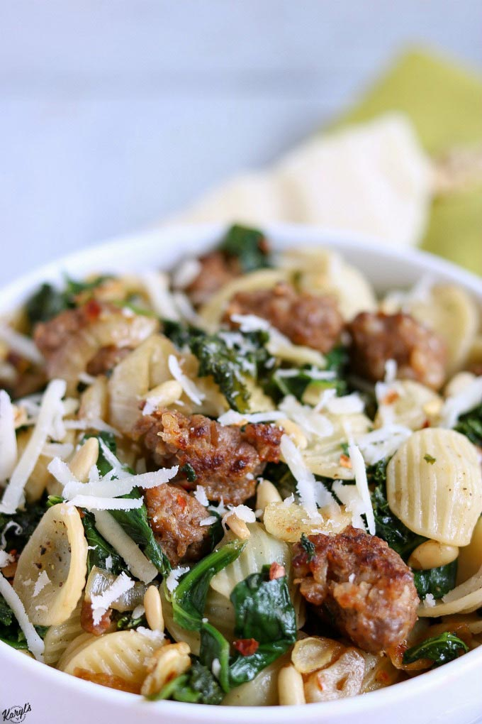 close up angle shot of finished Orecchiette with Sausage, Kale, Garlic and Pine Nuts in a white bowl with a green napkin in the background