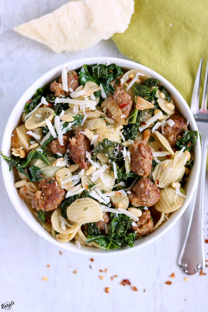 overhead shot of finished Orecchiette with Sausage, Kale, Garlic and Pine Nuts in a white bowl with a fork on the right hand side