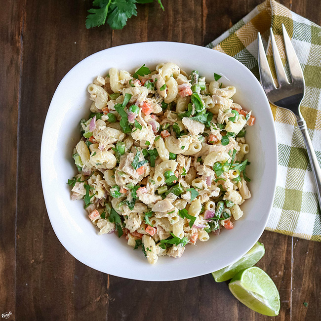 overhead shot of finished tuna pasta salad in a white bowl with a fork on the side