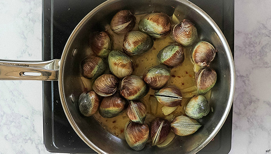 overhead shot of clams steaming in pot