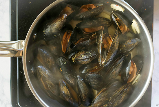 overhead shot of mussels steaming in pot