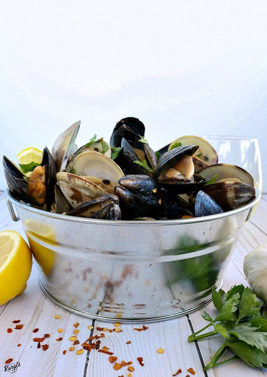 picture of clams and mussels in metal bucket, with lemons, garlic, parsley & red pepper flakes on table and glass of wine in background