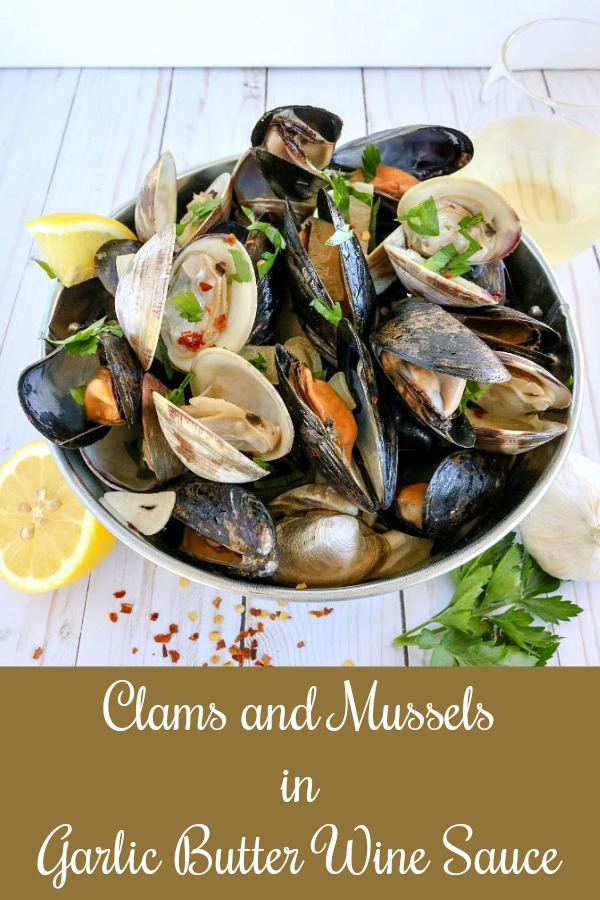 picture of clams and mussels in metal bucket, with lemons, garlic, parsley & red pepper flakes on table and glass of wine in backgriound