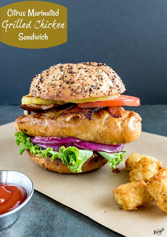 close up shot of finished grilled chicken sandwich on a piece of brown paper with tater tots and ketchup on the side