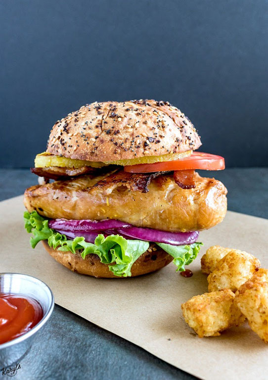 front shot of finished grilled chicken sandwich on a piece of brown paper with tater tots and ketchup on the side