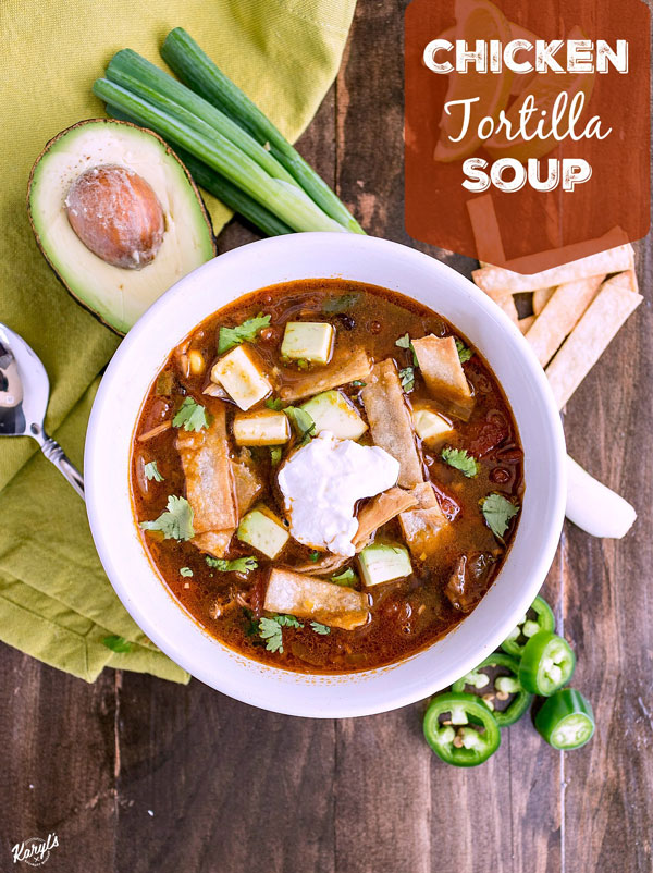 Chicken Tortilla Soup will warm you up with tender chicken, lots of veggies, and a bold kick from the spices. Finish with homemade tortilla strips, diced avocado, a little sour cream and sharp cheese. Ready in under 30 minutes on the stove, or in the crock pot after a long day #chicken #corn #blackbeans #jalapeno #tortillastrips #chickentortillasoup #spicysoup #easyrecipe #comfortfood #karylskulinarykrusade