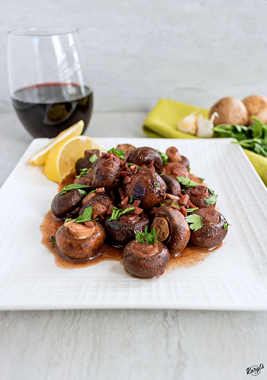 up close shot of finished red wine garlic mushrooms on a white plate with a glass of wine in the background