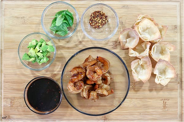 overhead process shot: Shrimp Avocado Wonton Cups ingredients in glass bowls on a wooden board