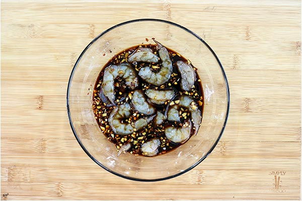 overhead process shot: shrimp and marinade in a glass bowl