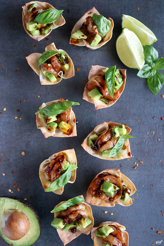 overhead shot of finished Shrimp Avocado Wonton Cups on a black board with avocado and lime wedges on the side