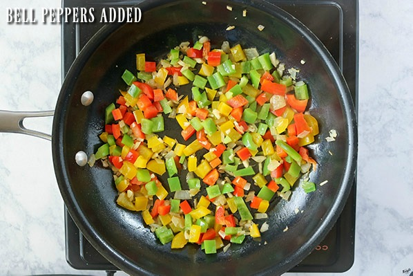 overhead process shot of peppers, onion and garlic in skillet