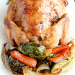 close up overhead shot of finished Roasted Cornish Game Hen with vegetables on a white platter