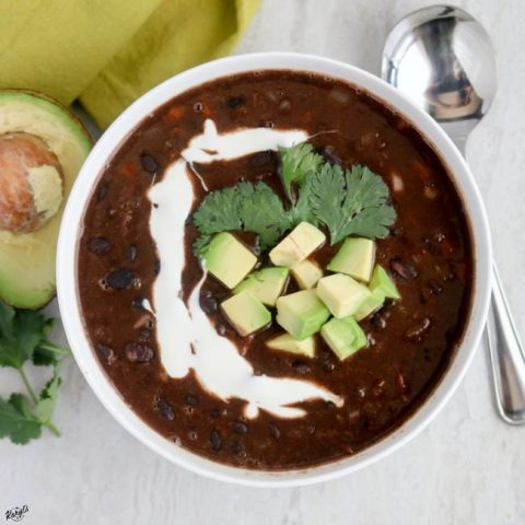 overhead shot of a white bowl with black bean soup with half an avocado and a metal spoon on the side