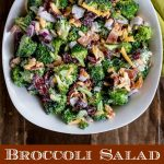 overhead shot of finished Broccoli Salad in a white bowl, with green napkin on the side