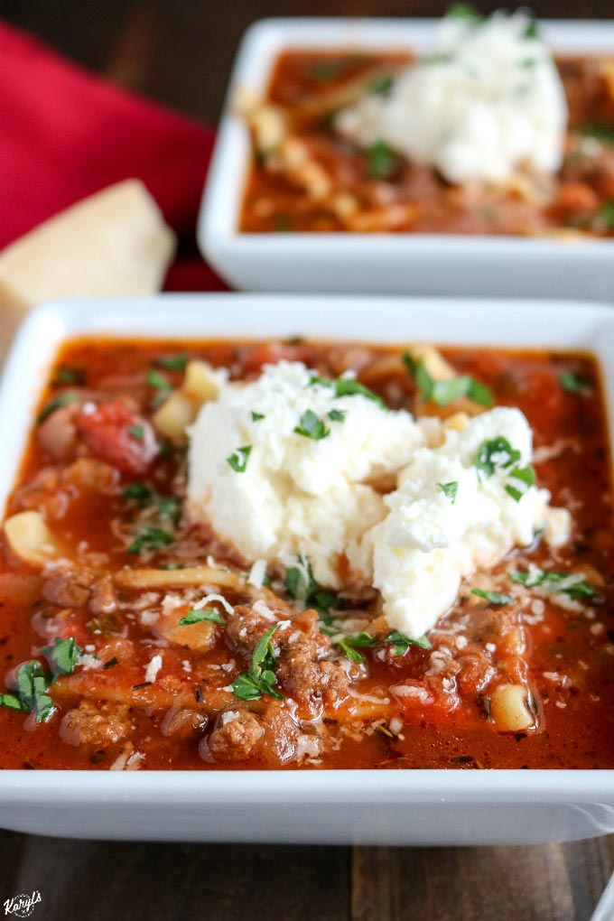close up angeled shot of 2 white bowls filled with venison lasagna soup and topped with ricotta mixture