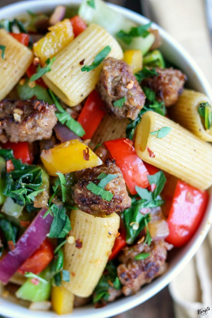 Italian Sausage Bell Pepper Pasta is a hearty, delicious meal in a bowl. Spicy Italian sausage adds wonderful flavor and a little heat to bright peppers and onions, and hearty greens #sausage #pasta #bellpeppers #onions #spicysausage #italiansausage #skilletmeal #karylskulinarykrusade
