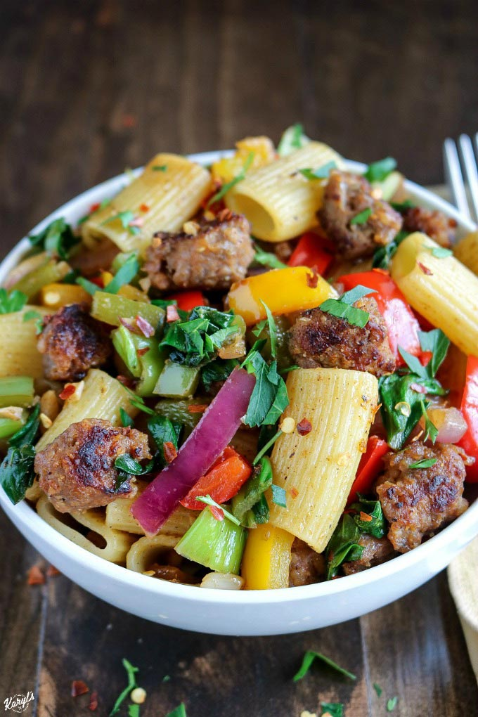 Italian Sausage Bell Pepper Pasta combines spicy sausage with peppers, onions and hearty greens for a delicious meal in a bowl #sausage #pasta #bellpeppers #onions #spicysausage #italiansausage #skilletmeal #karylskulinarykrusade