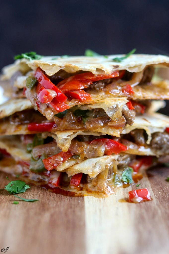 head on shot of quesadillas, quartered and stacked, on serving board