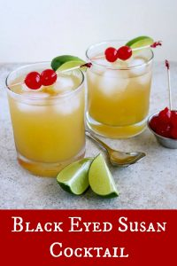 2 glasses of Black Eyed Susan, with lime wedges in front, stirring spoon and maraschino cherries on the side