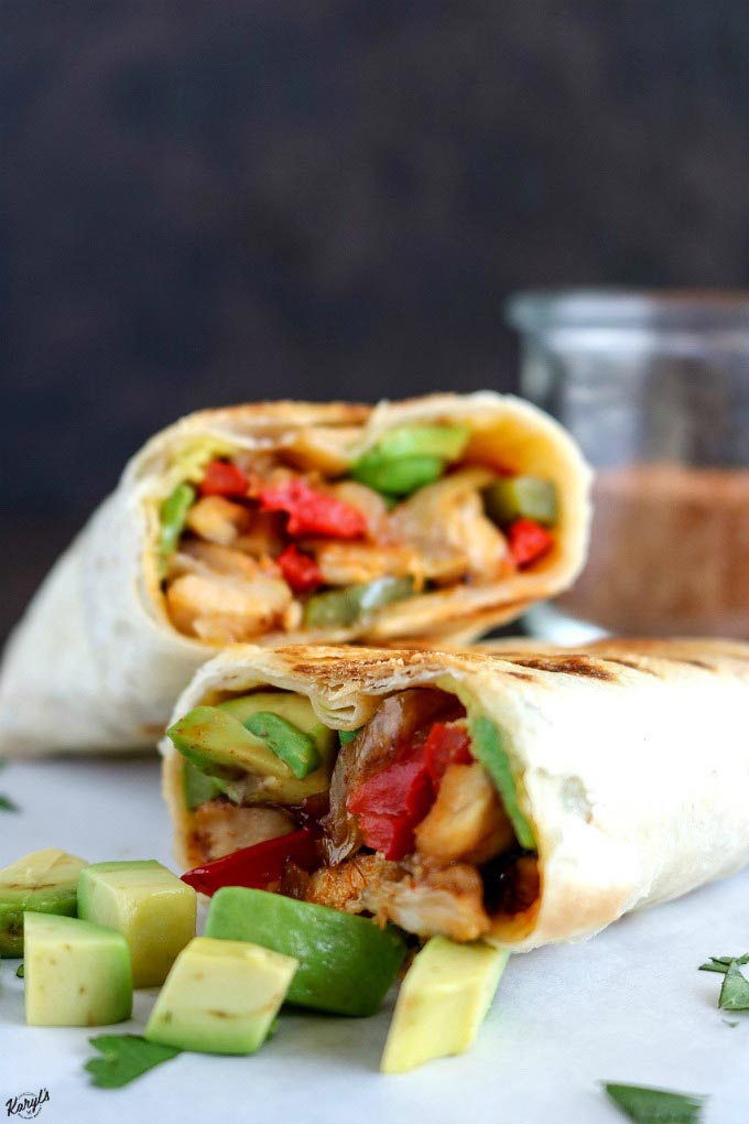 Finished chicken fajita wrap cut in half and one half leaning against the other, with avocado on the side