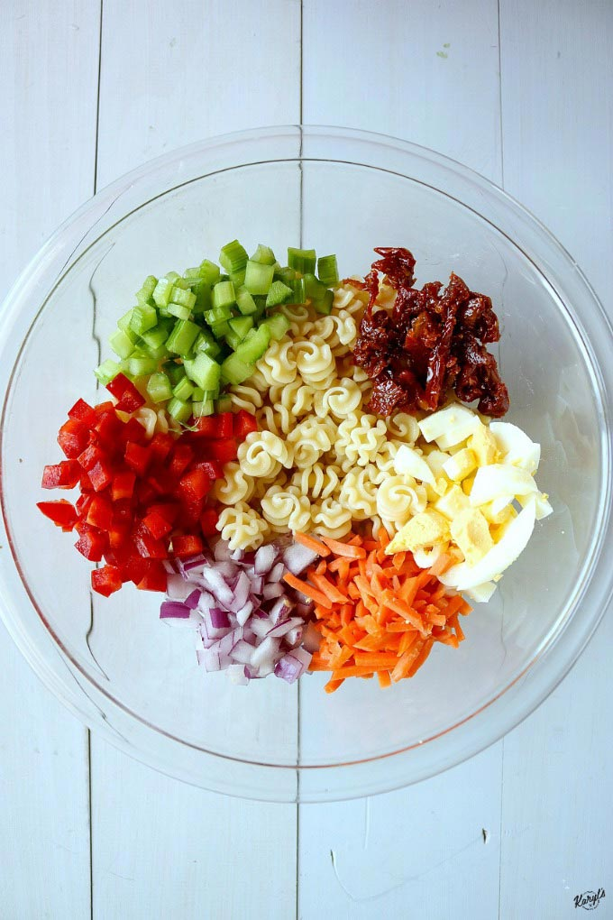 macaroni salad ingredients in a clear bowl
