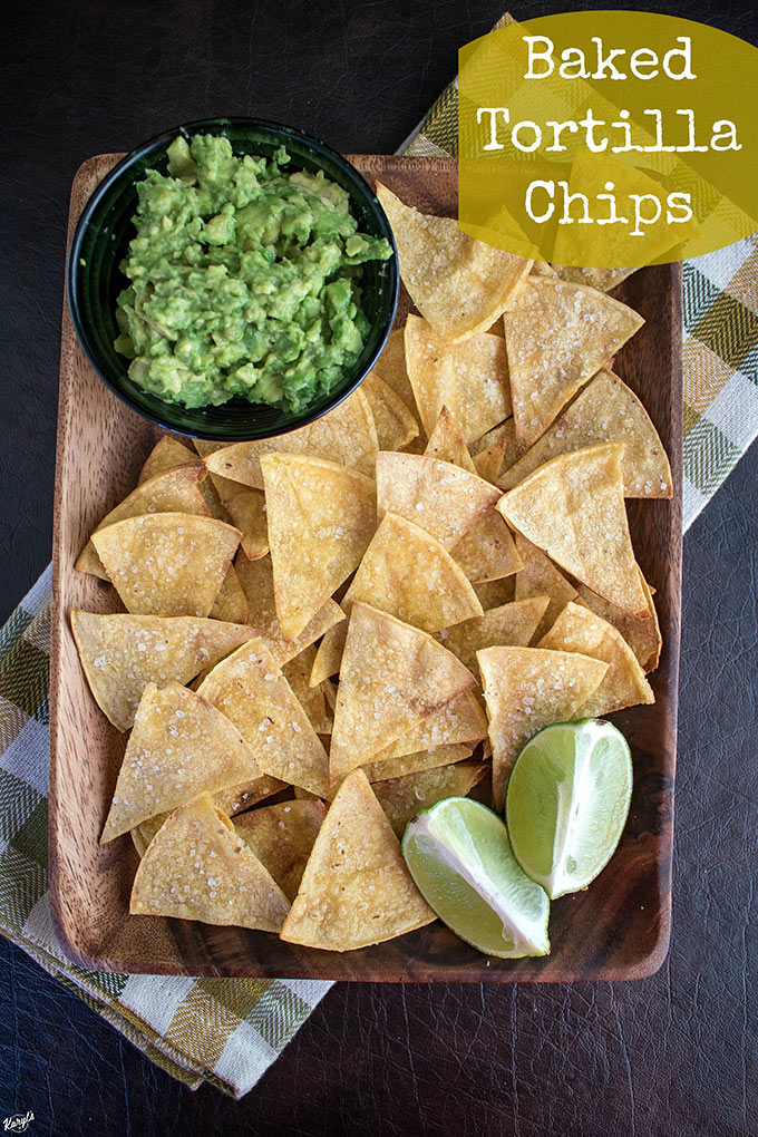 Overhead shot of a plate of Baked Tortilla Chips with a side of guacamole and lemon wedges