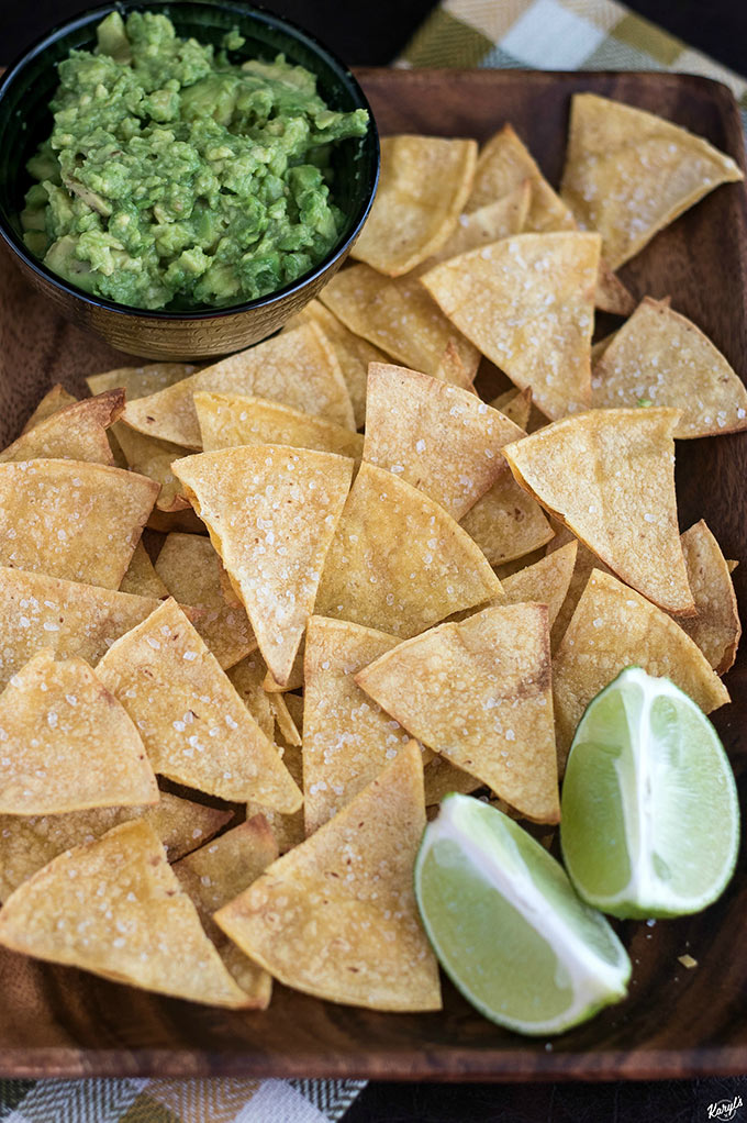 Close up shot of a plate of Baked Tortilla Chips with a side of guacamole and lime wedges