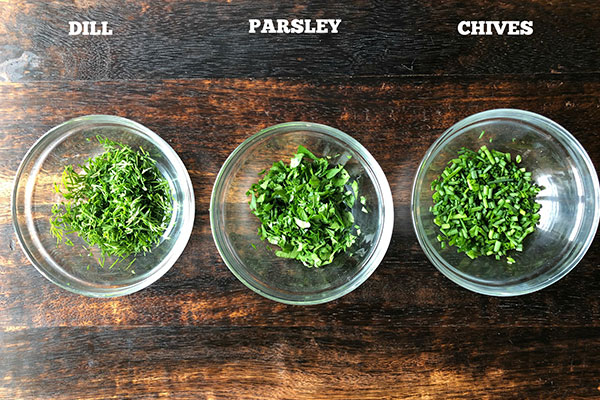 overhead shot of herbs chopped in glass bowls