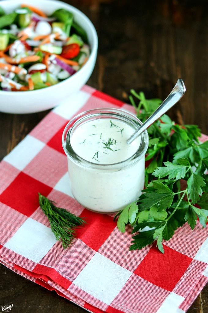 overhead shot of Coconut Milk Ranch Dressing in a glass jar with a spoon, on a plaid napkin with salad in teh background
