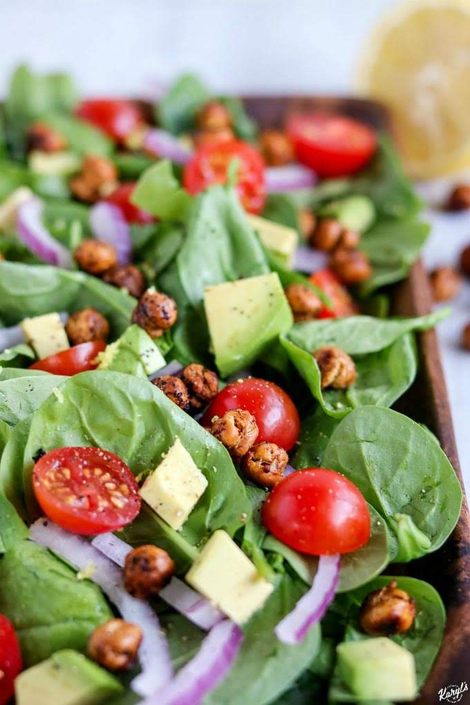 Roasted Chickpea Spinach Salad is light, healthy, vegetarian and gluten free! It packs a punch with a great combination of flavors and textures. Perfect as a complement to a main course dish, or on its own as a quick and easy lunch or dinner. #babyspinach #avocado #tomatoes #chickpeas #roastedchickpeas #salad #spinachsalad #roastedchickpeaspinachsalad #vegetarian #glutenfree #meatless #meatlessmonday #karylskulinarykrusade