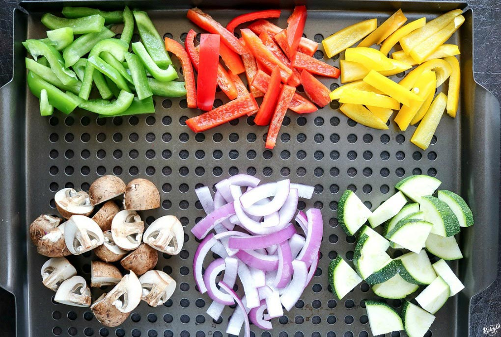 overhead shot of raw vegetables in piles on a grill plate