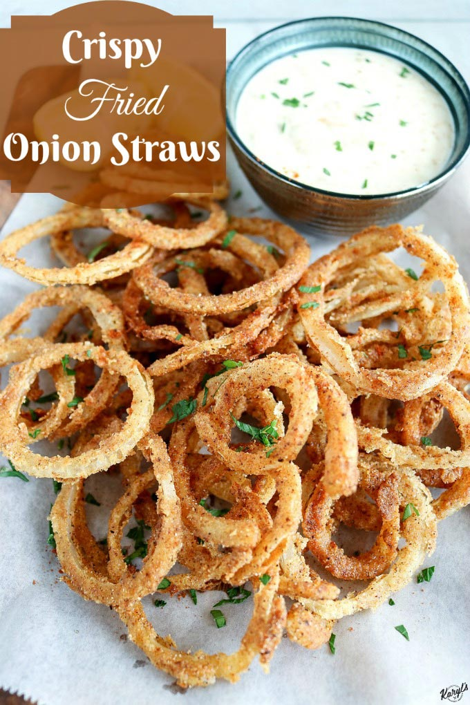 overhead shot of Crispy Fried Onion Straws on a piece of white parchment paper, with side of garlic aoili in top right corner