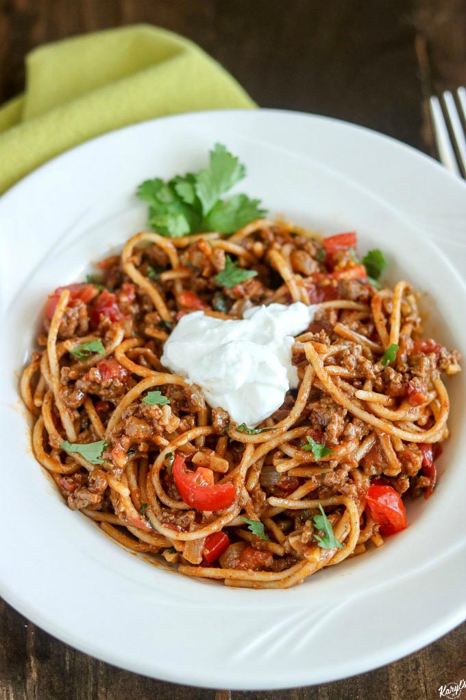 close up shot of taco spaghetti in a white bowl, topped with sour cream