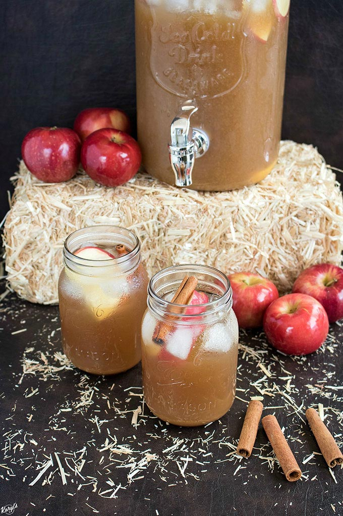 finished rum punch in mason jars  with bale of hay in the background, plus apples and cinnamon sticks as props and dispenser full of rum punch in the background