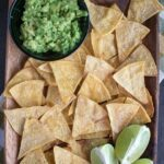 overhead shot of a plate of baked tortilla chips with guacamole and limes on the side