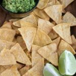 close up shot of baked tortilla chips with lime and guacamole on the side