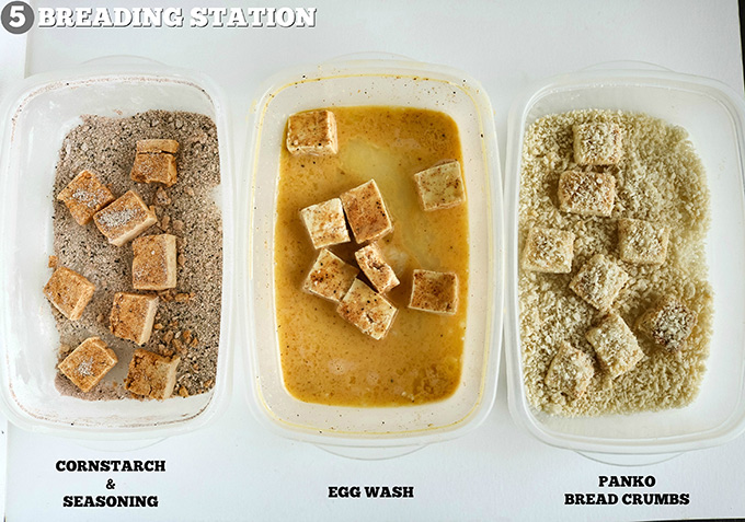 overhead shot of tofu in breading station containers