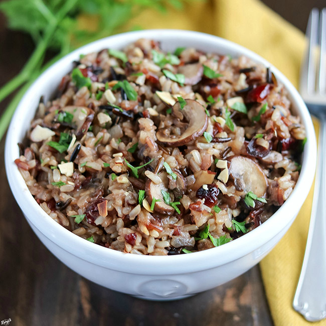 Mushroom Wild Rice Pilaf in white bowl with fork and napkin on right side