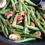 close up shot of finished Green Bean Mushroom Saute in a black skillet