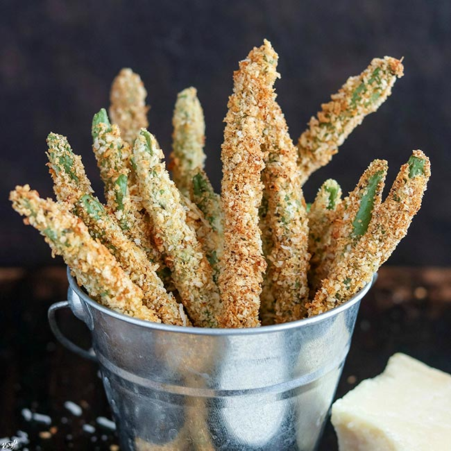 finished Baked Green Bean Fries in a tin bucket, with a wedge of parmesan on the side
