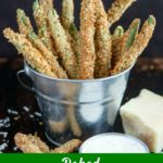 close up shot of Baked Green Bean Fries in a metal bucket with a side of ranch and a chunk of parmesan cheese