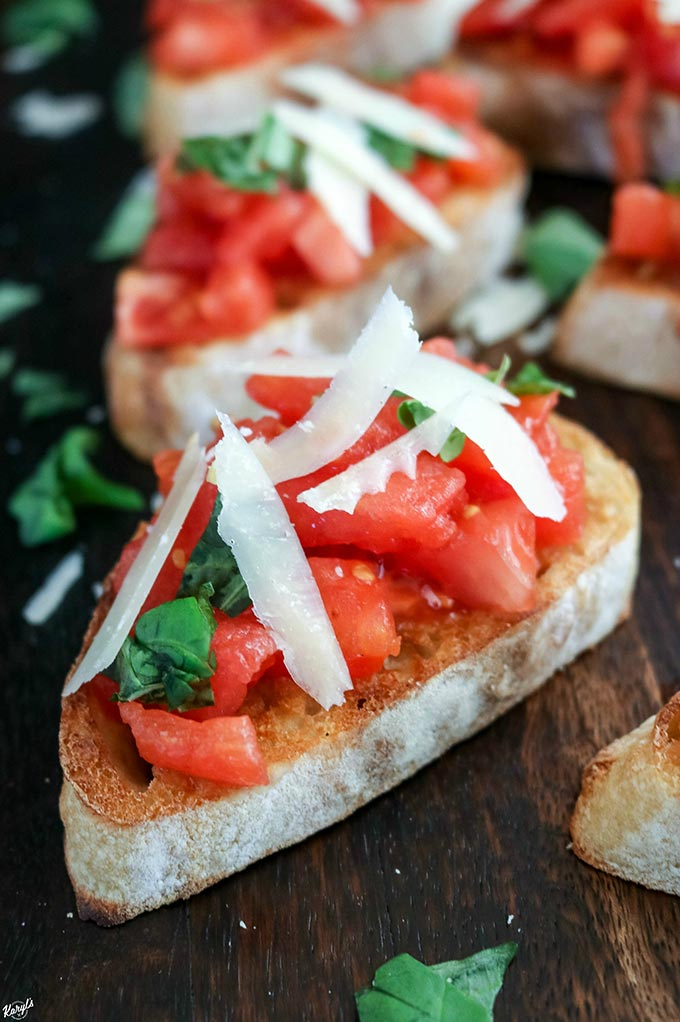 Traditional Bruschetta combines a few simple, quality ingredients for an amazingly flavorful appetizer. These delicious bites are easy to make and hold well, making them perfect for entertaining or even as a snack #tomatoes #vinetomatoes #parmigianoreggiano #basil #italianbread #bruschetta #tomatobruschetta #traditionalbruschetta #appetizer #bitesized #fingerfood #karylskulinarykrusade