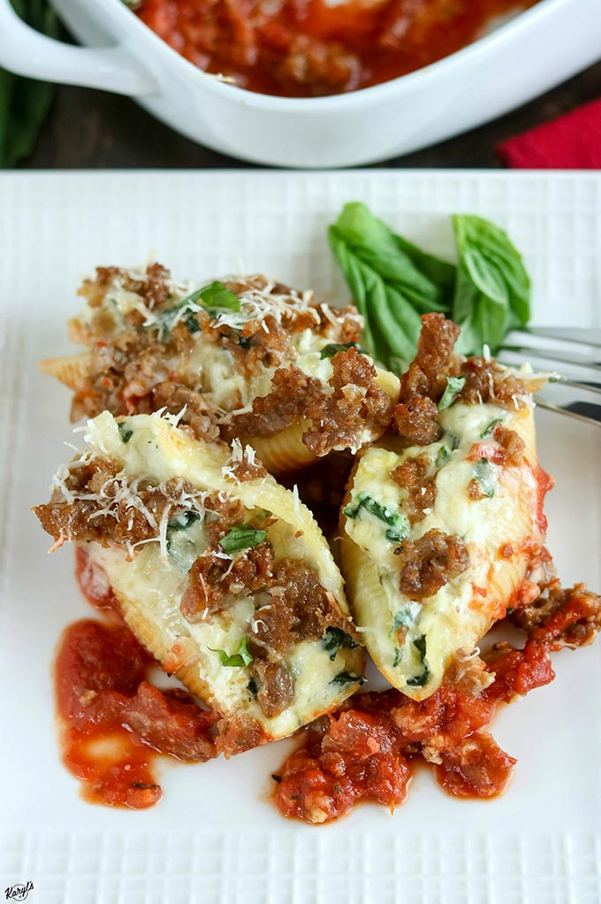 Close up shot of finished Sausage Spinach Artichoke Stuffed Shells on a white plate