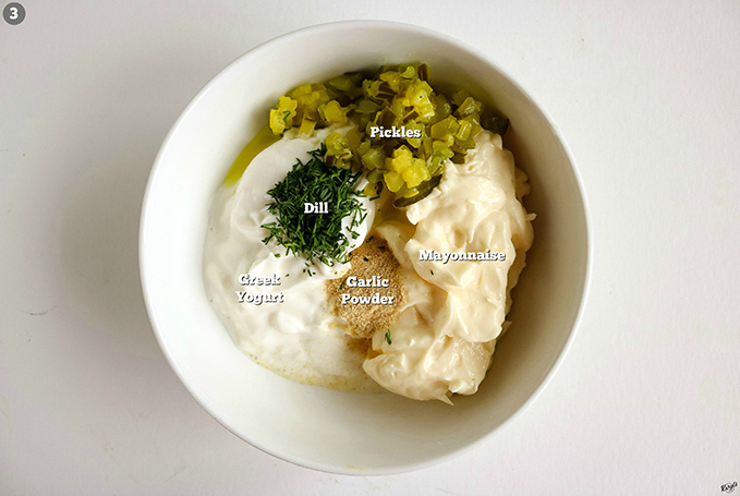 overhead shot of all tartar sauce ingredients in bowl with ingredients listed
