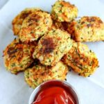 overhead shot of a stack of Baked Zucchini Carrot Tots on white paper with a side of ketchup