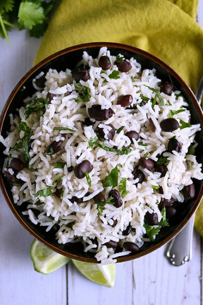 overhead shot of rice in black bowl with napkin and fork on the side, with cilantro in background